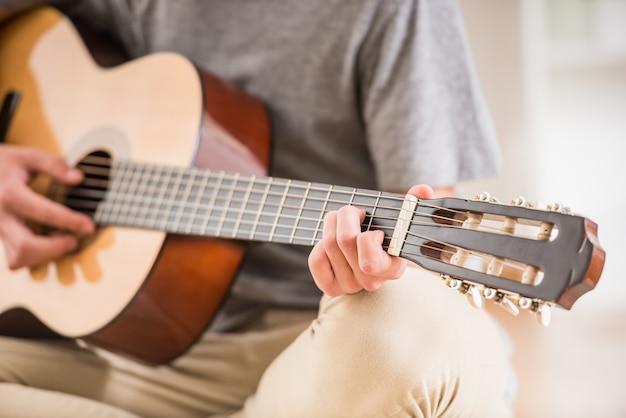 Het close-up van tiener zit thuis en speelt gitaar. Premium Foto