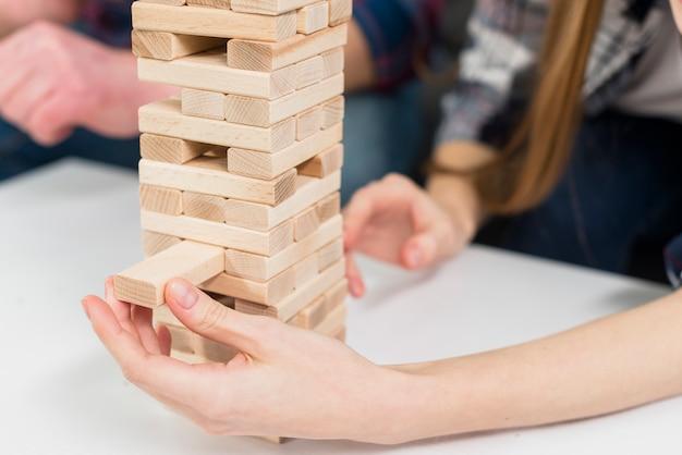 Het close-up van vrouw verwijdert zorgvuldig een blok van de het verwarren houten toren Gratis Foto