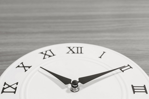 Het close-updeel van witte klok verfraait voor tien over tien uur op houten bureau Premium Foto