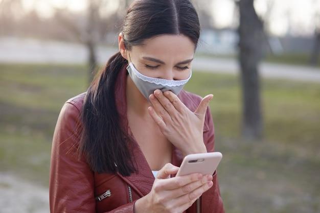 Het close-upportret van aanbiddelijke het glimlachen brunette met moderne slimme telefoon in handen, leest goed nieuws in sociaal netwerk over coronavirus pandemie Premium Foto