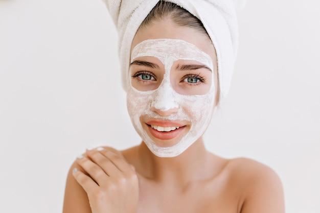 Het close-upportret van de mooie jonge vrouw die met handdoeken glimlacht na nemen bad maakt kosmetisch masker op haar gezicht. Gratis Foto