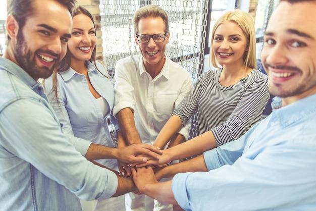 Het commerciële team in vrijetijdskleding houdt samen handen. Premium Foto