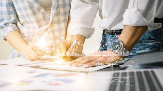 Het commerciële teamwerk die de technologiewereld analyseren van het grafiekennetwerk het bureaunotitieboekje op de houten presentatie van het lijstidee. Premium Foto