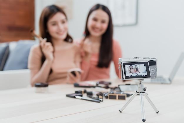 Het concept van beautyblogger-influencer gebruikt camera's om op te nemen en live te streamen naar sociale netwerken bij het gebruik van cosmetica als een nieuw bedrijf in het new normal-tijdperk. focus op camera. Premium Foto