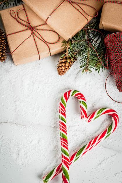 Het concept van de kerstmistijd, kerstboomtakken, denneappels, giften en traditioneel het snoepriet van nieuwjaarsnoepjes, op een witte marmeren lijst met sneeuw. copyspace bovenaanzicht Premium Foto