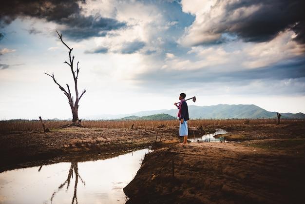 Het concept van de watercrisis, hopeloze en eenzame landbouwer zit op gebarsten aarde dichtbij droogend water. Premium Foto