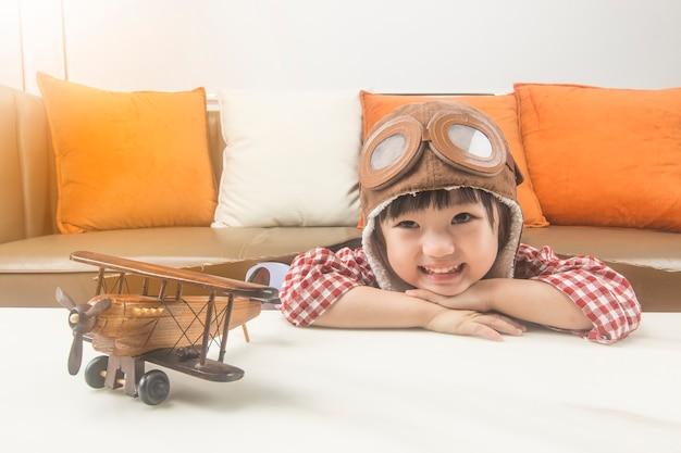 Het concept van dromen en reizen. het kind speelt de rol van een piloot en droomt ervan de ruimte in te vliegen. Gratis Foto