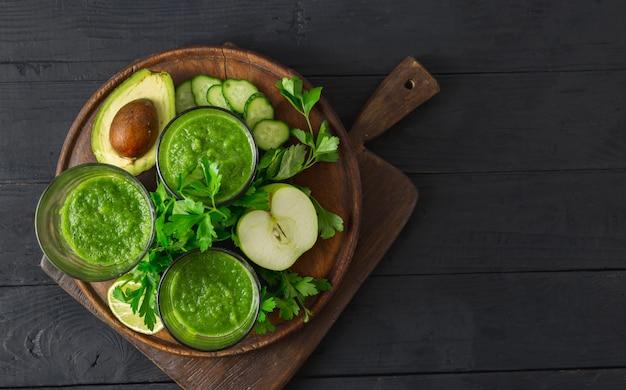 Het concept van het detoxdieet, groene smoothie op een houten hoogste mening als achtergrond Premium Foto