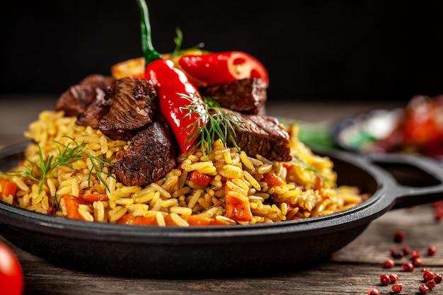 Het concept van oosterse gerechten. nationaal oezbekistaans pilau met vlees in een gietijzerkoekepan, op een houten lijst. achtergrond afbeelding. bovenaanzicht, kopie ruimte, plat leggen Premium Foto