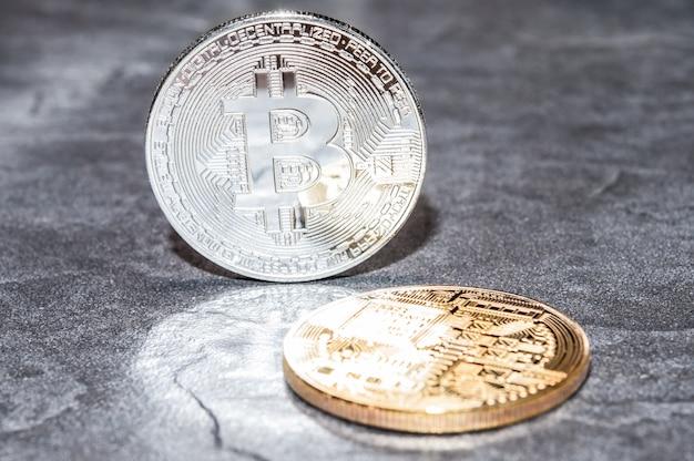 Het concept van zilver en goud bitcoin op een stenen achtergrond. Premium Foto