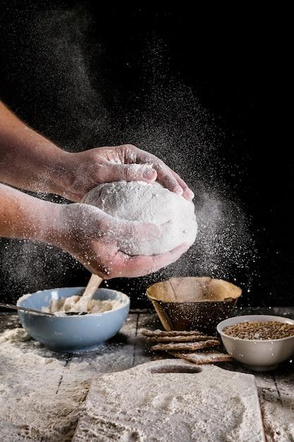 Het deeg van de mannelijke bakker bestrooien deeg met bloem Gratis Foto