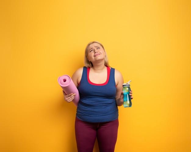 Het dikke meisje doet thuis gymnastiek. vermoeide uitdrukking Premium Foto