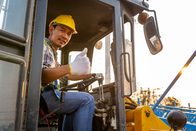 Het drijven van arbeider zware tractor op wielen, wielladergraafwerktuig met backhoe het lossen zandwerken in bouwwerf. Premium Foto