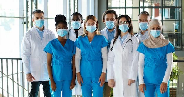 Het drukke team van gemengde rassen van mannelijke en vrouwelijke artsen die voor camera stellen en handen kruisen in het ziekenhuis. internationale groep medici in medische maskers. beschermde multi-etnische artsen en verpleegkundigen in kliniek Premium Foto