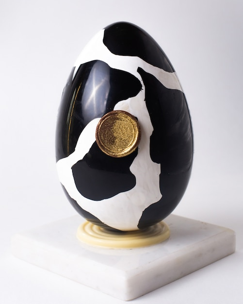 Het ei van de vooraanzichtchocolade bij koe zwart-wit kleuren op tribune Gratis Foto