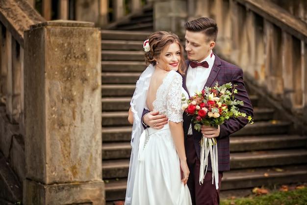 Het elegante bruid en bruidegom stellen samen in openlucht op een huwelijksdag Premium Foto