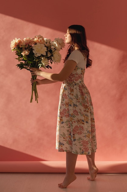 Het elegante dame stellen met bloemboeket Gratis Foto