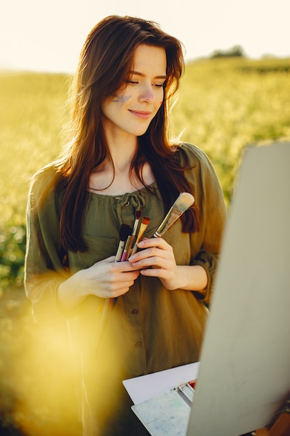 Het elegante en mooie meisje schilderen in een gebied Gratis Foto