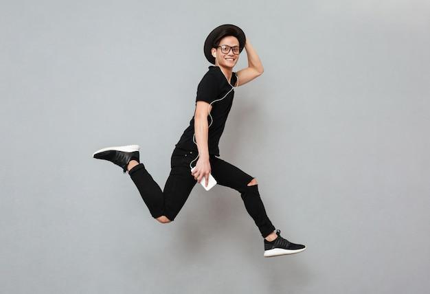 Het emotionele jonge aziatische mens geïsoleerd springen Gratis Foto