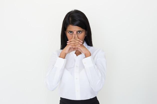 Het ernstige indische meisje stellen met clasped handen bij gezicht Gratis Foto
