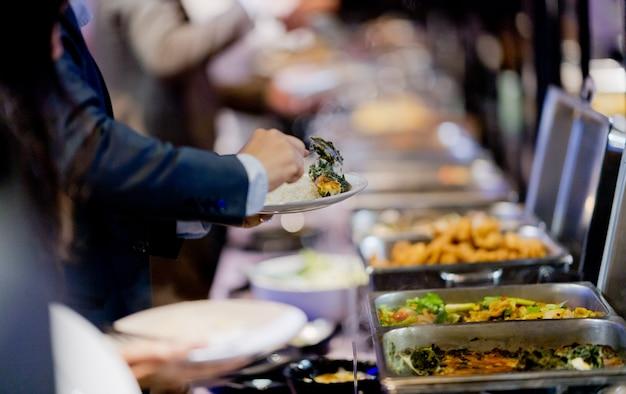 Het eten opscheppen, buffet eten in het restaurant, catering Premium Foto