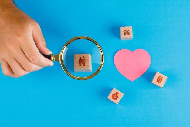 Het familieconcept met document gesneden hart op blauwe lijstvlakte lag. hand met vergrootglas over houten kubus. Gratis Foto