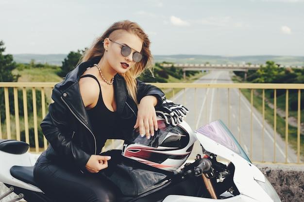 Het fietsermeisje in leer kleedt zich op een motorfiets Gratis Foto