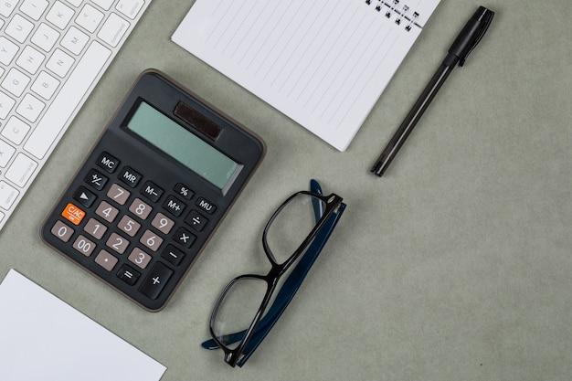 Het financiële concept met notitieboekje, document, pen, calculator, toetsenbord, glazen op grijze vlakte als achtergrond lag. Gratis Foto