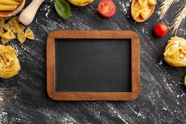 Het frame van de ongekookte deegwarenregeling op zwarte achtergrond met houten frame Gratis Foto