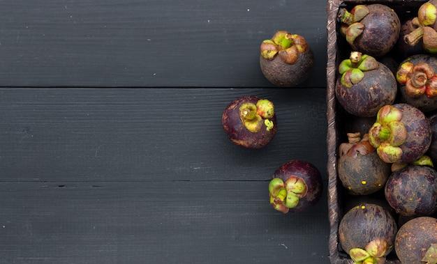 Het fruit van de close-upmangostan op zwart hout Premium Foto