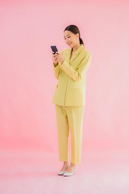 Het gebruik van portret mooie jonge aziatische bedrijfsvrouw slimme mobiele telefoon met koffiekop op kleur Gratis Foto