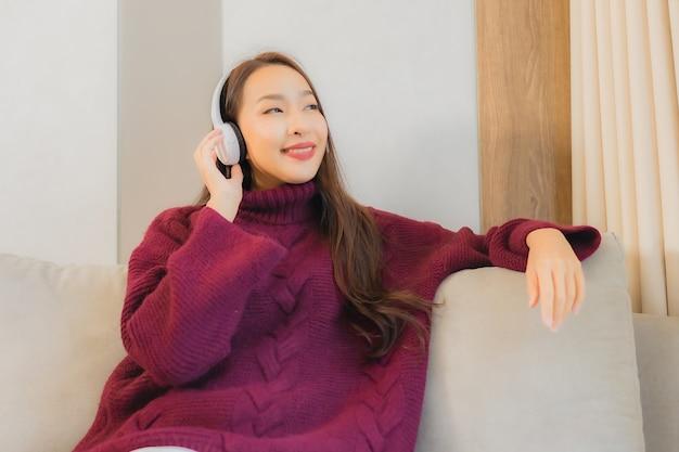 Het gebruikshoofdtelefoon van de portret mooie jonge aziatische vrouw om muziek op bank in woonkamerbinnenland te luisteren Gratis Foto