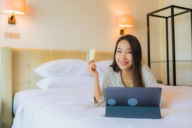 Het gebruikstablet van de portret mooie jonge aziatische vrouw met creditcard op bed Gratis Foto