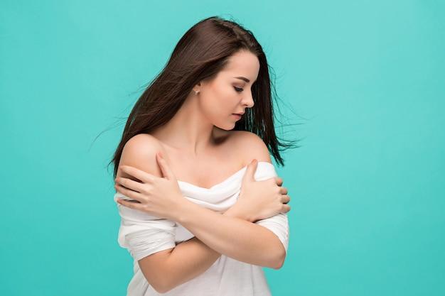 Het gefrustreerde jonge vrouw stellen op blauw Gratis Foto