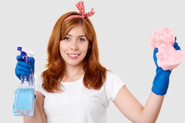Het geïsoleerde schot van tevreden vrouwelijke conciërge houdt nevel en spons, draagt hoofdband, wit t-shirt en beschermende rubberen handschoenen, klaar voor het schoonmaken, staat binnen. huishoudelijk en hygiëneconcept Gratis Foto