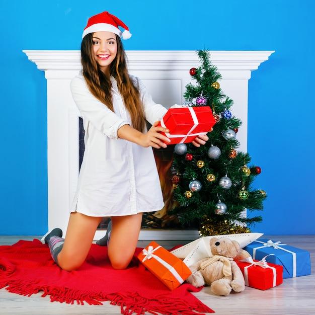 Het gekke glimlachende meisje dat kerstmis opent stelt voor. zitten bij open haard en met nieuwjaar versierde boom. positieve emoties en geluk. Gratis Foto