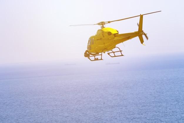 Het gele helikopter vliegen, blauwe hemel en witte wolken Premium Foto