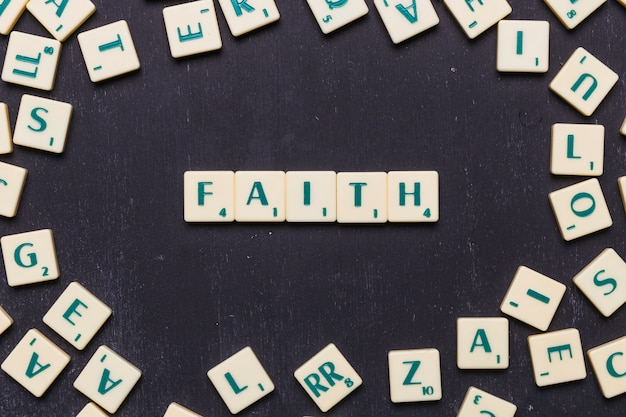 Het geloof graait brieven over zwarte achtergrond Gratis Foto