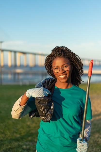 Het gelukkige afrikaanse amerikaanse vrijwilliger stellen in stadspark Gratis Foto