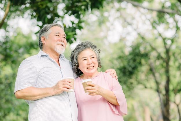 Het gelukkige aziatische hogere ouder paar drinkt samen koffie buiten in park Premium Foto