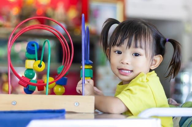 Het gelukkige aziatische kindmeisje spelen met veel speelgoed in de ruimte thuis. Premium Foto