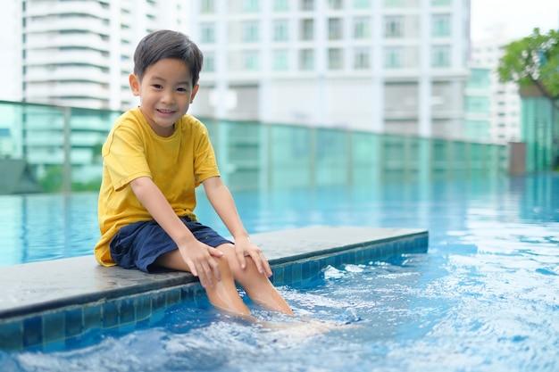 Het gelukkige aziatische zwembad van de jongenszitting Premium Foto