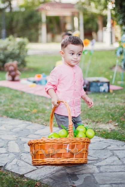 Het gelukkige babyjongen spelen in de tuin op een zonnige dag Premium Foto
