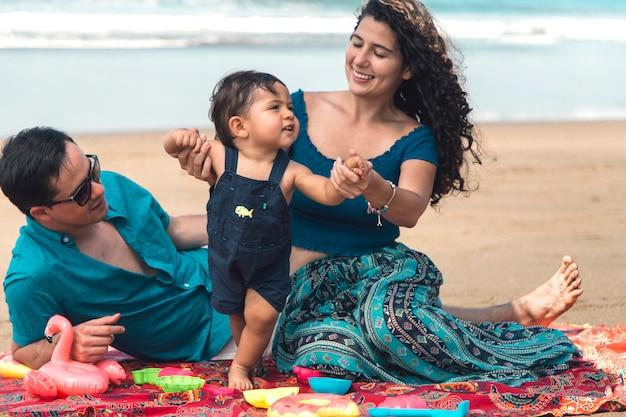 Het gelukkige familie spelen en baby die op strand leren te lopen Gratis Foto