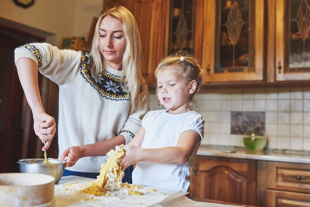 Het gelukkige glimlachende mamma in de keuken bakt koekjes met haar dochter. Gratis Foto