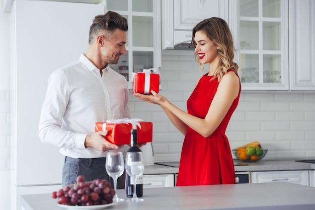 Het gelukkige glimlachende man en vrouwen geven huidig aan elkaar op vakantie Gratis Foto
