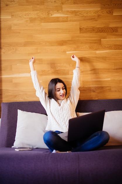 Het gelukkige jonge aantrekkelijke vrouwenwerk die thuis wapens uitrekken om na zware dag te ontspannen Gratis Foto