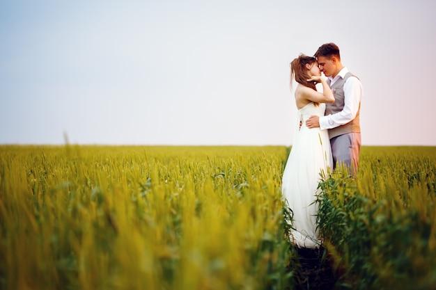 Het gelukkige jonge huwelijkspaar kussen Premium Foto