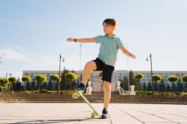 Het gelukkige jonge jongen spelen op skateboard in het park, kaukasisch jong geitje die stuiverraad berijden, die skateboard uitoefenen. Gratis Foto