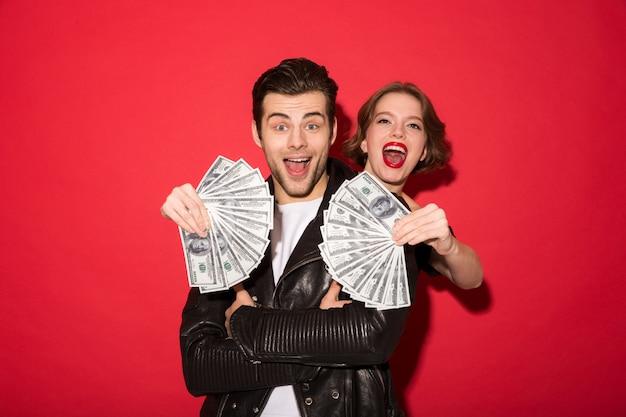 Het gelukkige jonge punkpaar stellen met geld Gratis Foto
